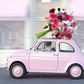 Une voiture rose avec des fleurs sur le toit